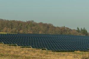 Solarfeld mit Windkraftanlage im Hintergrund